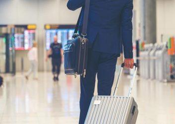 Mann mit Koffer am Flughafen